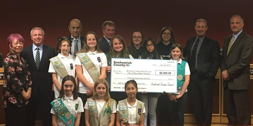Girl Scouts troop holding check with and Terry Ryan
